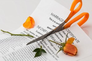 A pair of scissors cutting a marriage certificate