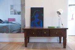 Wo ma'n home gallery (Roma), salotto e camera da letto –Una scrivania in legno con appoggiata una fotografia e alle spalle di questo un vetro da cui si intravede la camera da letto.