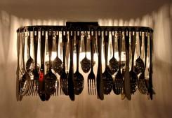 alt: struttura base della lampada metallica in cromo lucido decorata da forchette, cucchiai e coltelli in acciaio inox