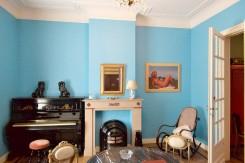 Una delle stanze della casa di Magritte: il soggiorno dalle pareti turchine, con caminetto, piano verticale, tavolo tondo e sedia a dondolo