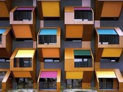 la facciata di un palazzo caratterizzata dalle tende di colori diverse sui balconi