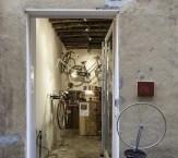 """Veduta dall'esterno di Opera Unica, la porta di ingresso con accanto una copia della celebre opera di Duchamp """"Ruota di Bicicletta"""". La porta dello spazio è aperta e si intravede l'interno."""