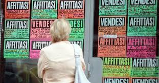 Una donna legge i cartelli di affitto e vendita immobili, dietro la vetrina di un'agenzia
