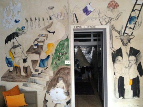 una parete dipinta e al centro una porta aperta dove si intravede un'altra stanza