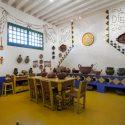 pavimento giallo come anche il tavolo e sedie poste al centro, decorazioni sulla parte alta delle pareti