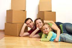 genitori e figlia sorridenti sdraiati sul pavimento e scatoloni da trasloco