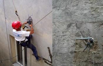 edilizia acrobatica operatore effettua intervento sulla facciata di palazzo con imbragatura e funi di sicurezza