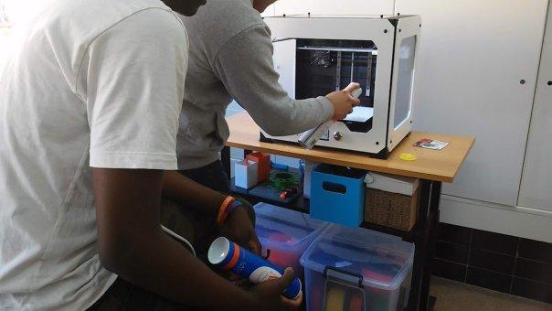 Fotografía de alumnos pulverizando laca sobre la base de impresión