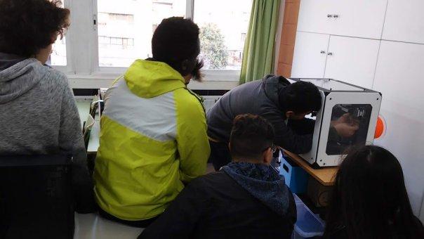 Fotografía de un alumno manipulando el extrusor de la impresora mientras los demás miran