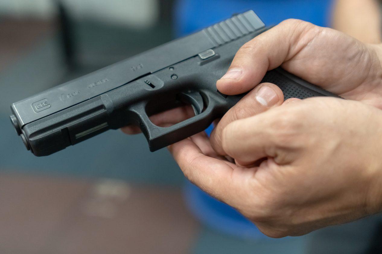 A hand of man practicing firing using a Glock gun model at the shooting range. Fire glock hand gun.