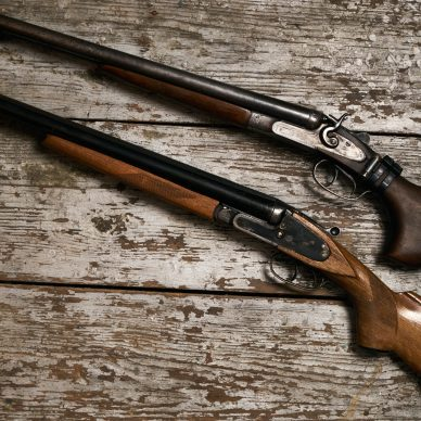 Two old antique shotguns rifle on wooden table background, close-up. Top view of a hunting equipment