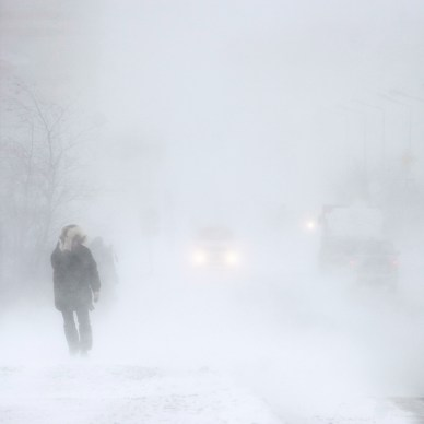 Snowstorm in the city. A man during a blizzard is walking along the street. Cars on a snowy road. Strong wind and snowfall. Arctic climate. Extreme North. Anadyr, Chukotka, Siberia, Far East Russia.