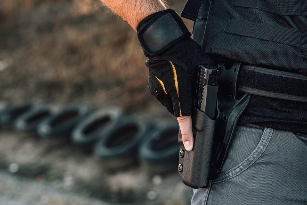 Pulling out a gun from the holster on belt, close-up.