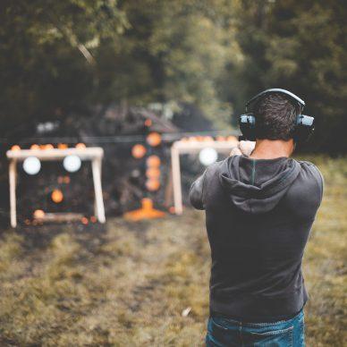 A shallow focus shot of a male shotting a gun at the gun range