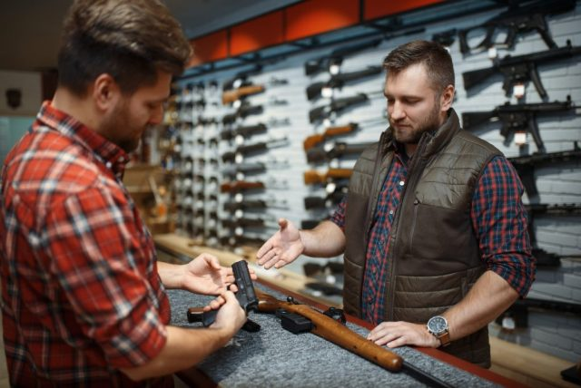 Man and owner choosing rifle and handgun in gun shop. Euqipment for hunters in weapon store, hunting and sport shooting hobby, security and selfdefence
