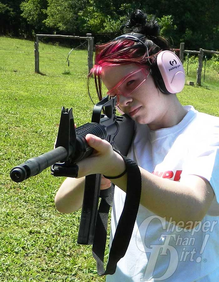 Young woman in white t-shirt and pink ear protection shooting a black AR-15 with CMMG .22 caliber conversion on a green grassy area with wooded area in the background.
