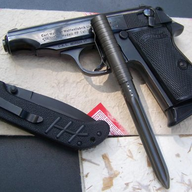 Black Walther, barrel pointed to the left, a black combat pen and a black knife.