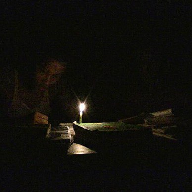 Picture shows a boy working by candlelight in a pitch black room.