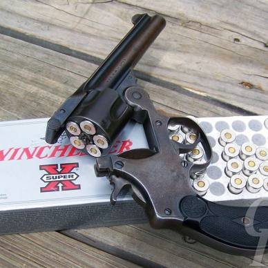 Black Smith and Wesson Perfected Model revolver laying on top of a silver case of Winchester ammunition on light gray wood boards