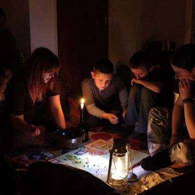 Picture shows a family playing a board game by lantern light in a room with no electricty.