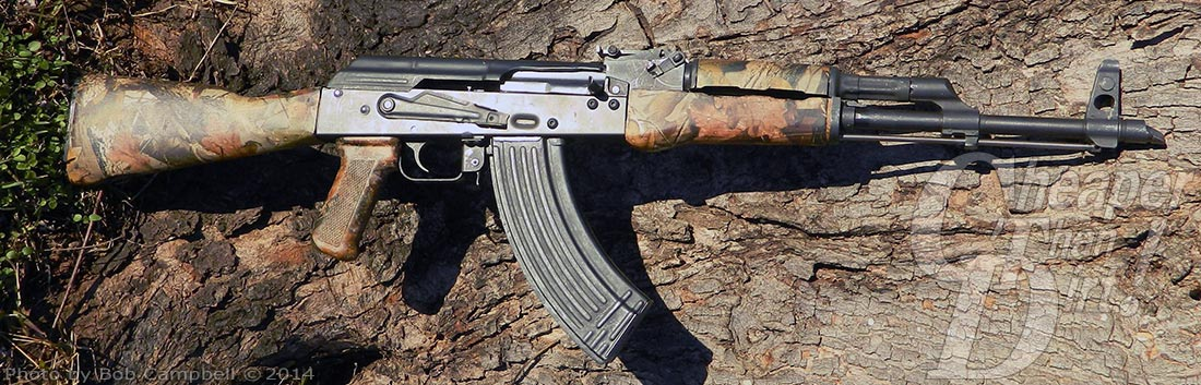 AK-47 with camo finish, barrel pointed to the right, lying on a log.