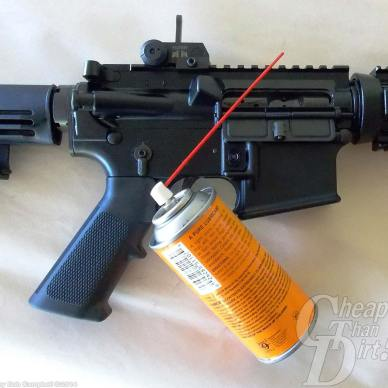 Black AR-15 on white background with orange can of lubricant
