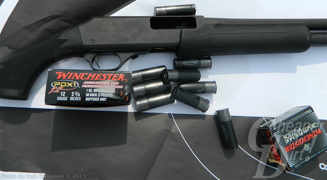 Shotgun laying across a target with Winchester PDX shells in posed position