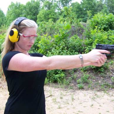 Woman shooting the CZ 9mm wearing yellow ear muffs