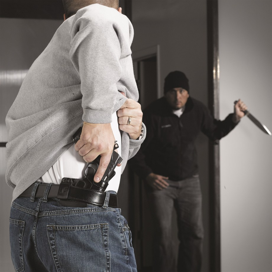 Attacker with a knife an man drawing his concealed pistol