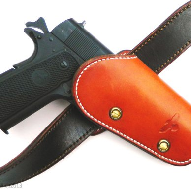 Black grip Colt Series 70 in Gunsite Omega holster in bright rusty brown on a belt