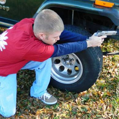 Young man in red shirt and jeans uses a vehicle to shield him while he practices