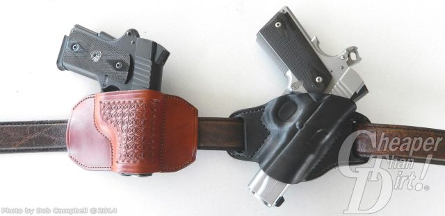 Two pistols in holsters, the one on the left is a medium brown concealed carry holster, the one on the right is a black concealed carry holster.