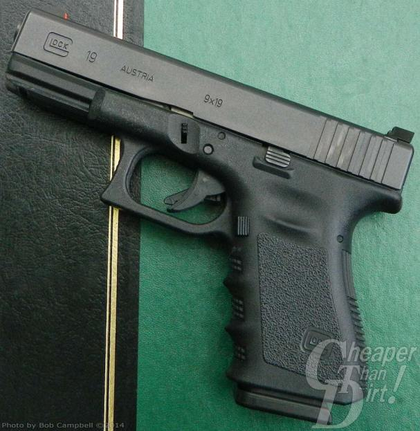 Black GLOCK 19, barrel pointed upward and to the left on a green desk blotter.