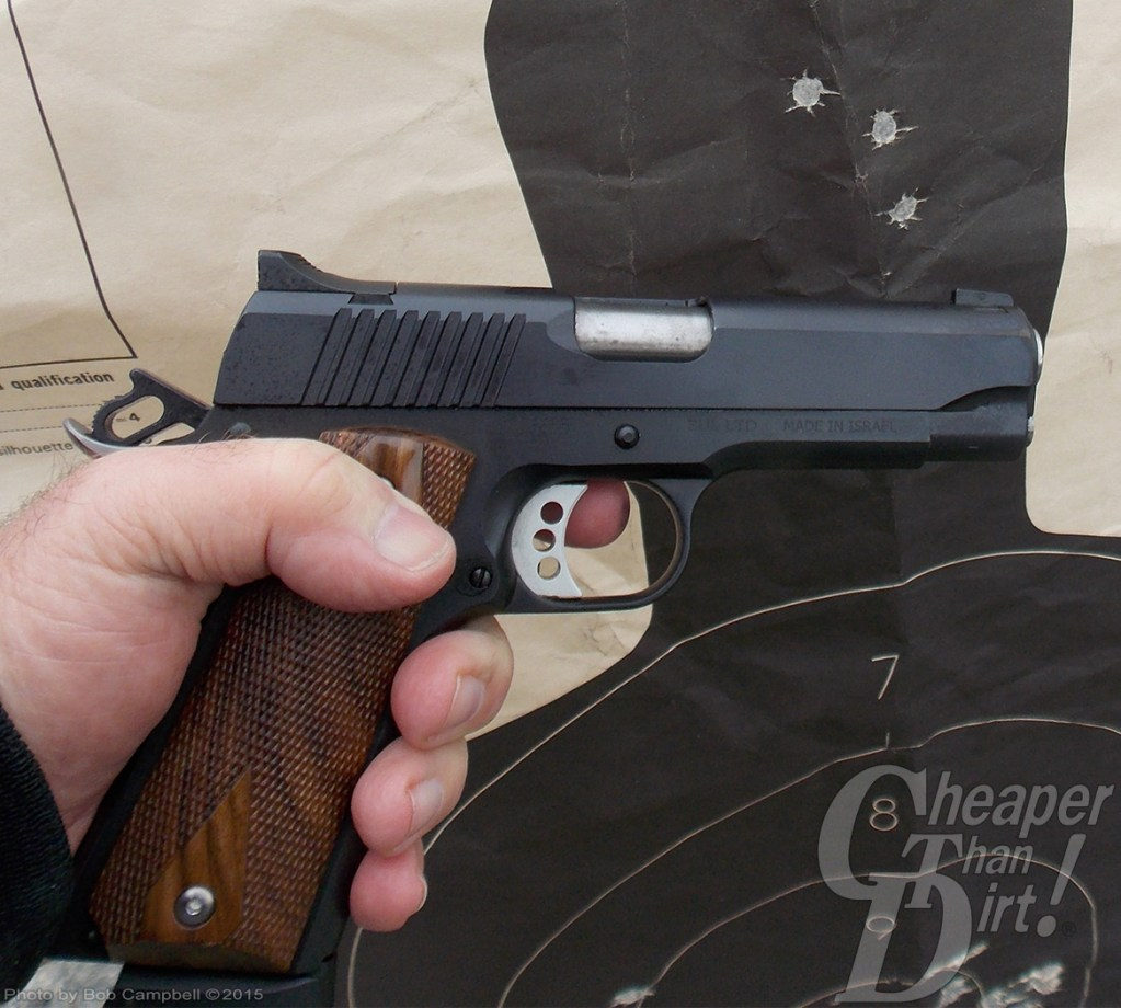 Author holding a black and wood gripped 1911 made by Magnum Research against a silhouette target.