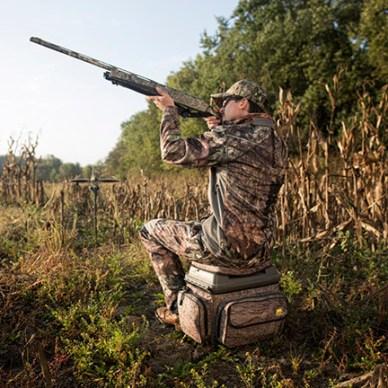 Hunter sitting on Plano 1812 Hunting Stool shooting a shotgun