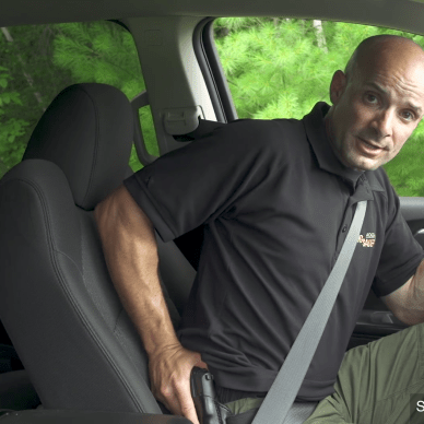 Man drawing a firearm while seatbelted in a car