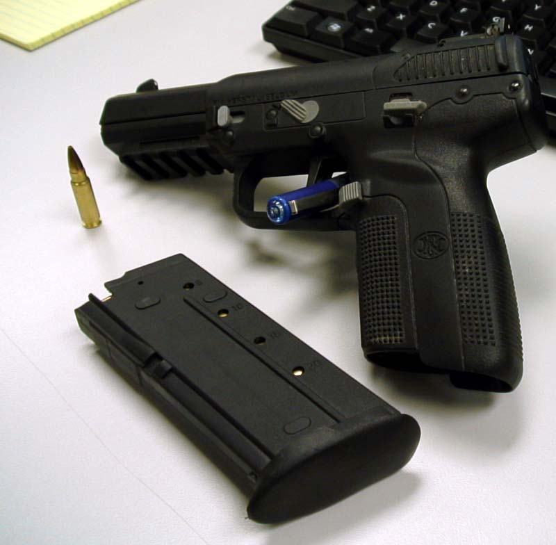 Black FN Five-seveN USG Pistol and black cartridge leaning against a black keyboard on a gray-to-white background