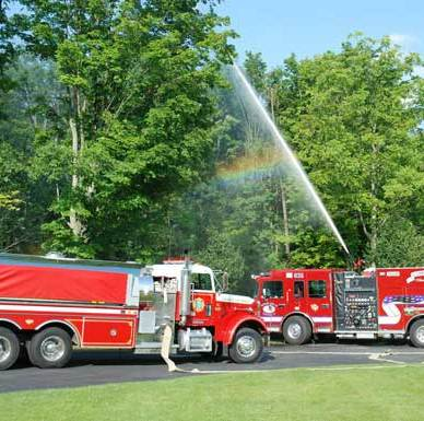 Two fire trucks with hoses charged.