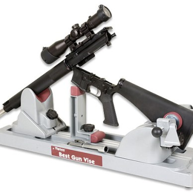 Black rifle on a white stand to hold it while cleaning on a white background