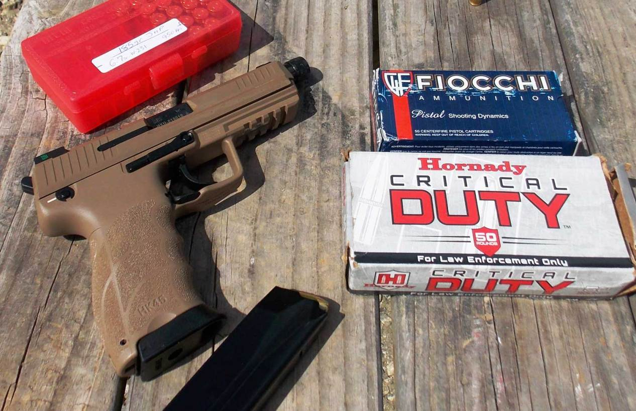 HK45 pistol in desert tan with boxes of ammunition