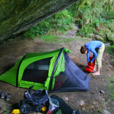 Picture shows a woman beside a tent, setting up camp under the shade of a rock overhang.