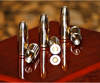 Six rounds of Liberty Ammunition Civil Defence ammunition of a wood surface.