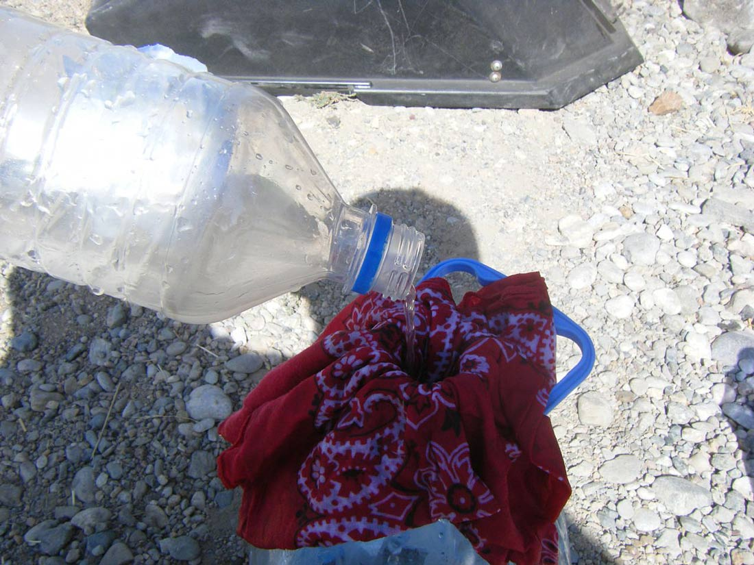 Picture shows water being filtered through a bandana into a water bottle.