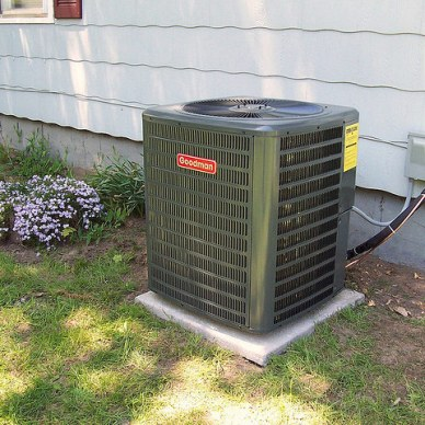 Picture shows a green a/c unit outside a white house.