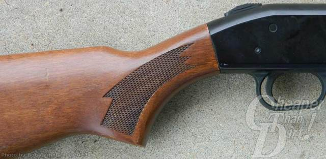 A Mossberg shotgun with a light brown checked stock on a gray cement'look background.