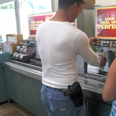 Man with a pistol on his hip refilling a drink at a restaurant.