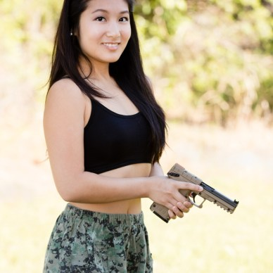 Asian woman holding a Kel-Tec PMR 30 handgun.