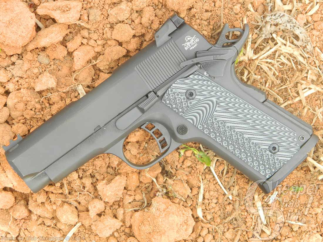 Silver/gray compact RIA and a reddish dirt background, muzzle pointed down and to the left