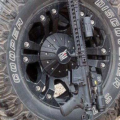 AR-15 rifle leaning against a tire