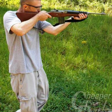 Light haired young man in gray t-shirt sghts the Mini 14 with a wooded area in the background